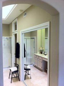 Large walk-in closet behind mirrored doors in Master Bath