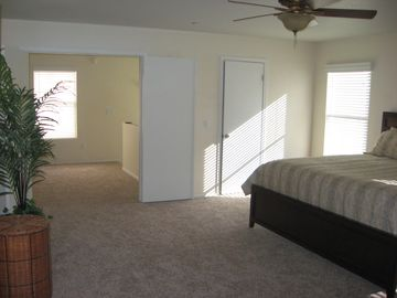 "The large master bedroom-- loft/stairway in background. Includes 41"" HDTV."