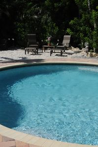 a sandy beach borders the solar heated pool