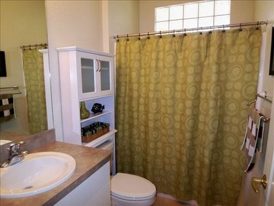 Adjoining Guest Bathroom. Full tub shower and space creating curved curtain rod.