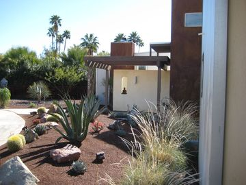 Across the desert landscaping to the front entrance of house.