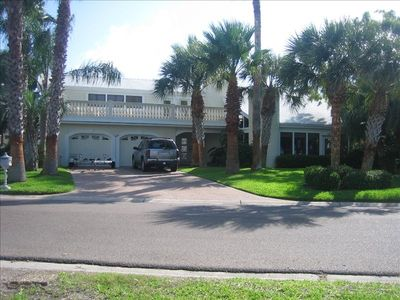 Front of house across from Aransas Bay with upper veranda & front patio in palms