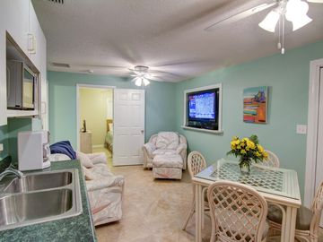 Lower level is complete with dining table, kitchenette, and entertainment center