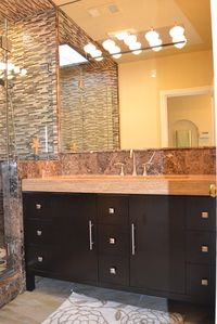 New bathroom with designer travertine vanity and high-end lighting.