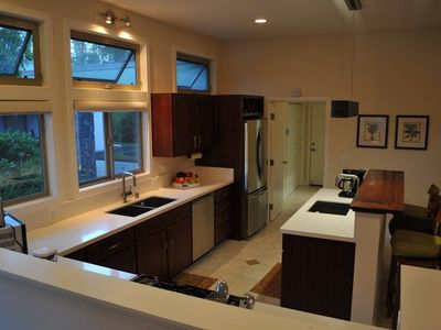 Kitchen with windows, two sinks, large fridge, propane stove top and dishwasher