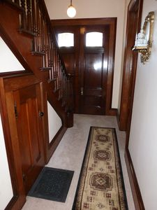 Hallway to upstairs features beautiful chestnut woodwork.