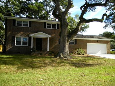 Two-story brick nestled under southern oaks