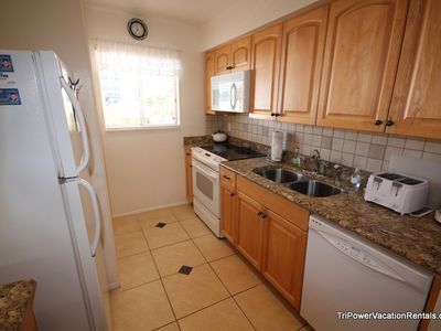 Upgraded kitchen including new applainces, granite counters and tile backsplash.