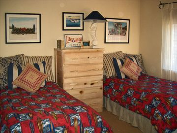 Guest bedroom with extra long twin beds, down quilts and sun balcony.