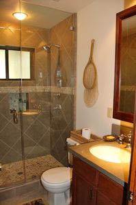 Shared downstairs bath. Shower spa, custom tile, river rock floor