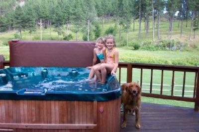 Guests enjoying the hot tub with Bailey the top dog at the ranch