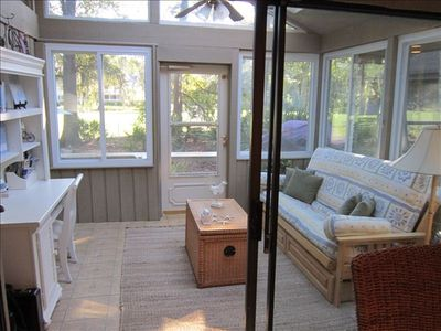 Inviting sunroom with full futon and desk, provides respite for relaxing