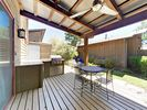 Outdoor Kitchen - The outdoor kitchen boasts a mini fridge, gas burner, and grill.