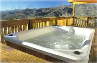 Four-person hot tub on wide porch with spectacular view of the Andrews valley