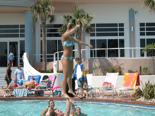 A group of cheerleaders practicing lifts in pool for the NCAA Championships. - Daytona Beach condo vacation rental photo