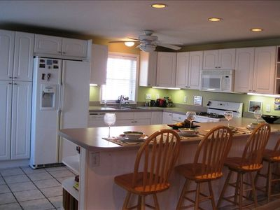 Large kitchen with breakfast bar, updated appliances and  tile floor.
