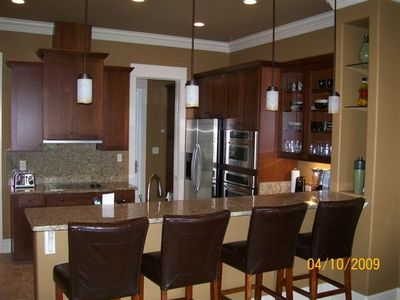 Kitchen w/ stainless appliances, granite counters, and 4 bar stools.