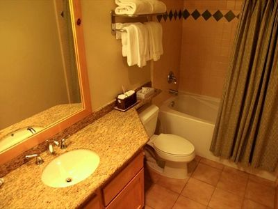 Bathroom with granite countertops and shower/tub combo