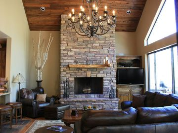 Show Low lodge rental - Living room with huge stone fireplace, wall of windows and open kitchen