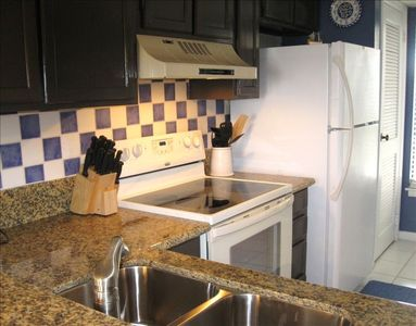 Fully equipped kitchen with clean new granite countertops.