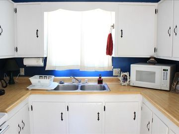 kitchen with coffeemaker, microwave, refridgerator, and stocked with all dishes