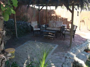 Covered patio with sandbox and comfortable seating