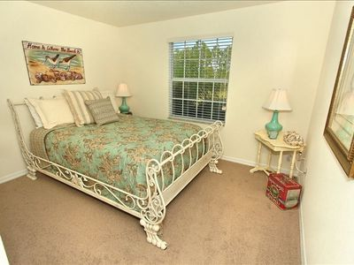 This upstairs queen bedroom features an ornate, wrought-iron bed.