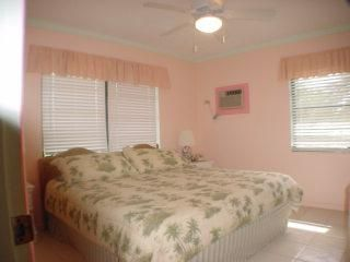King bedroom has en suite bathroom, tropical garden views, paddle fan, A/C. - Spanish Wells villa vacation rental photo
