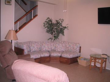 Living room with HD TV and comfortable recliners.
