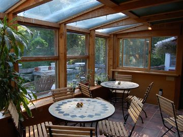 Breakfast sunroom next to cascading south-facing decks with bar-b-q.