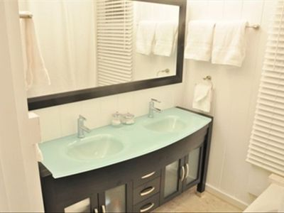 Upgraded bath with tile and glass top double vanity.