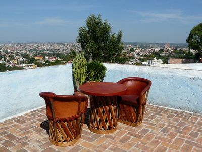 Terrace furniture includes umbrella and stand. La Parroquia in the background.