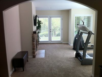 Master bedroom exercise alcove with TV, treadmill, and ellipical machine.