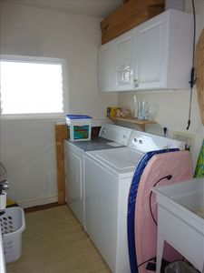 Laundry room with beach chair, towel, and boogie board storage