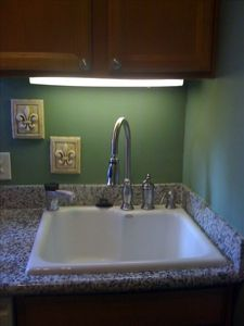 New kitchen with large Kohler sink, hot water dispenser, oak cabinets, granite