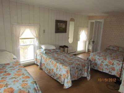 Large upstairs bedroom with two double beds and one single bed.