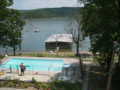 View from the screened in porch (40 yds to lake) - pool, trailer parking,dock.