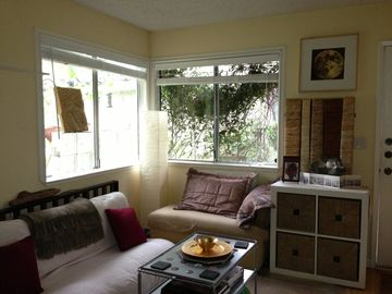 Capitola condo rental - cozy living room with ottomans, coffee table books, sofa pull out