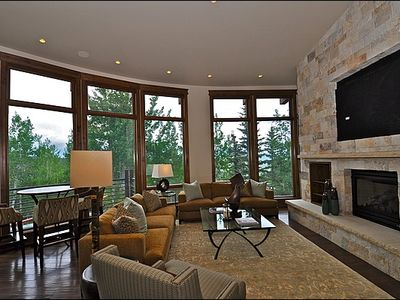 Living room with fireplace, large screen TV, and views of the slopes