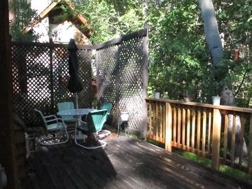 Secluded deck dining area, extra table and chairs available in closet.