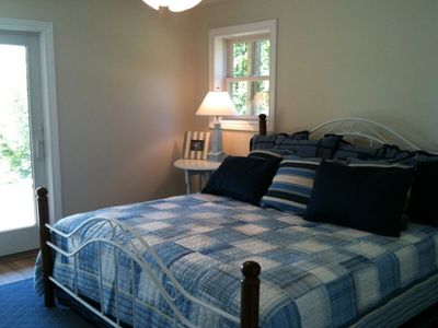 Walloon Lake house rental - Downstairs master with king bed, slider to bluestone patio and lake panorama