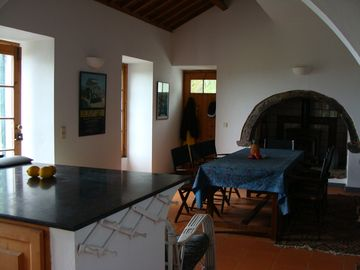wood stove alcove and refectory dinning table viewed from adjoining kitchen area