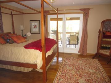 Master canopy bed, designer custom bedding, & doors opening to deck w lake view