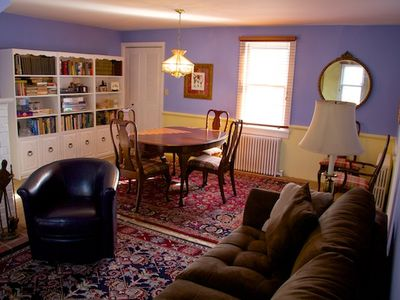 Dining room with seating for 6, bookcases w/ books and games.