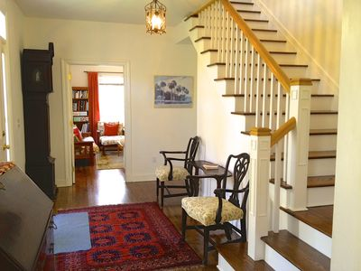 Elegant front entryway and staircase, newly refinished floors.