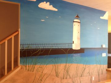 Mural in living room of Manistee lighthouse and pier