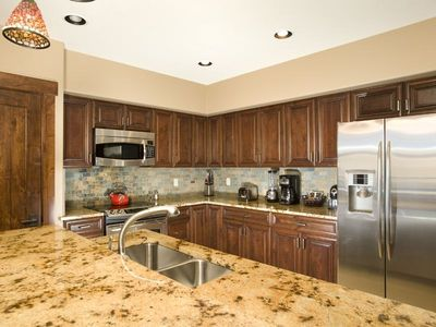 Modern kitchen equipped with stainless steel appliance and granite counter tops