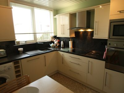 Newly fitted kitchen with dishwasher, garden view
