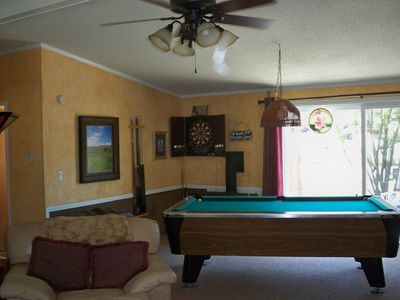 Pool, darts or step out to river view deck and hot tub..