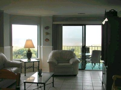 Living room leading to balcony and ocean